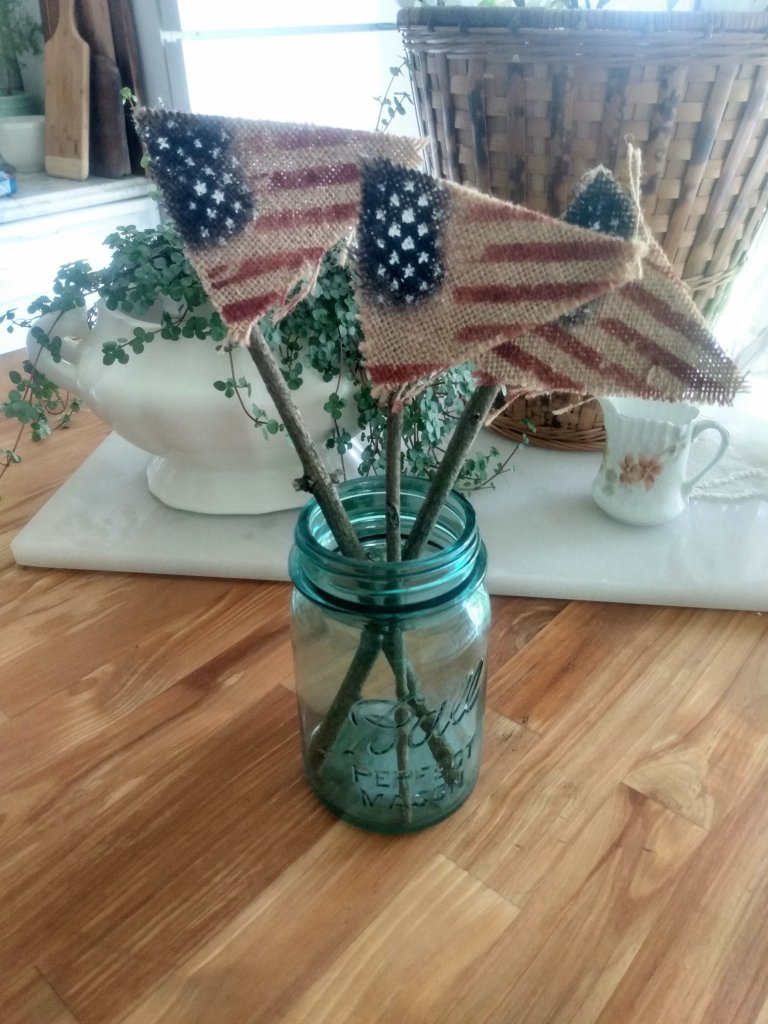 Diy Patriotic decor using burlap cut in triangles.  Then painted like a floag and glued to sticks.